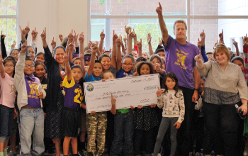 Students and teachers with a giant check