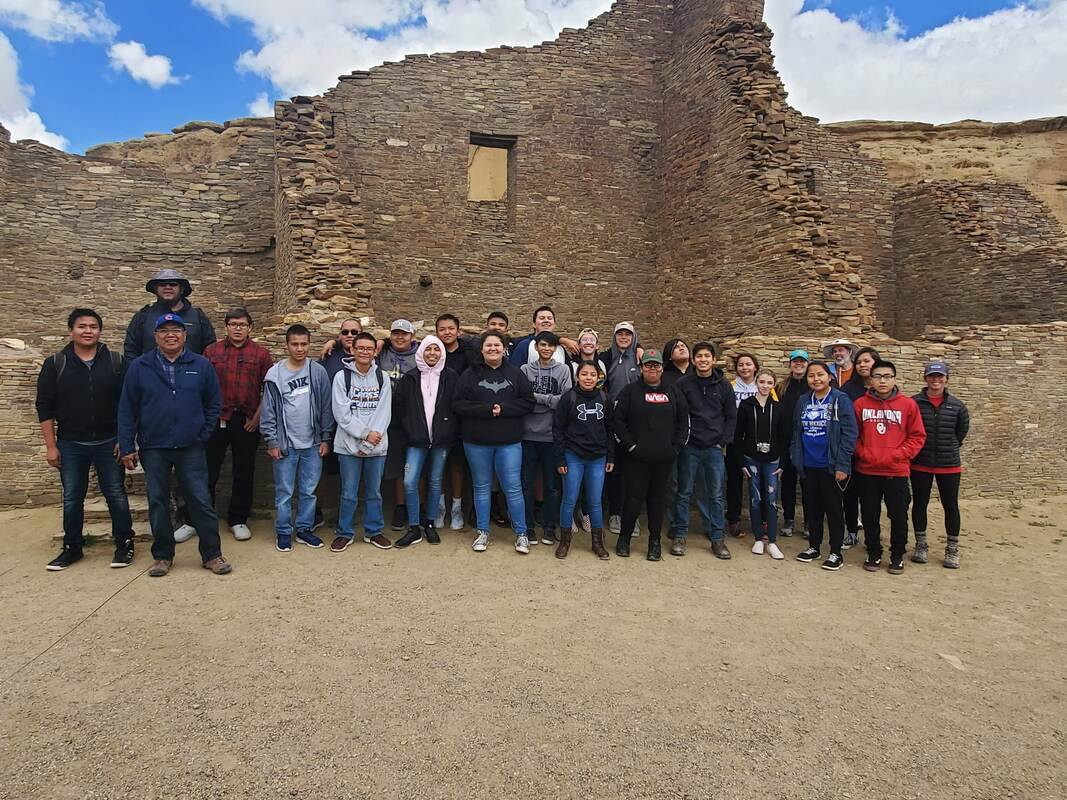 Students and teachers in front of some ruins
